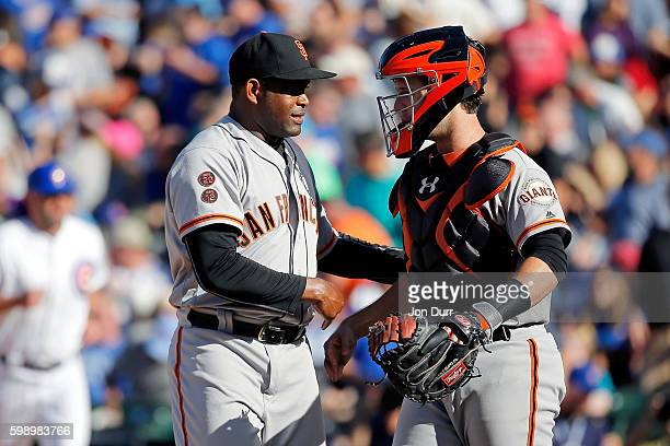 Santiago Casilla of the San Francisco Giants celebrates the win with Buster Posey at Wrigley Field on September 3 2016 in Chicago Illinois The San...
