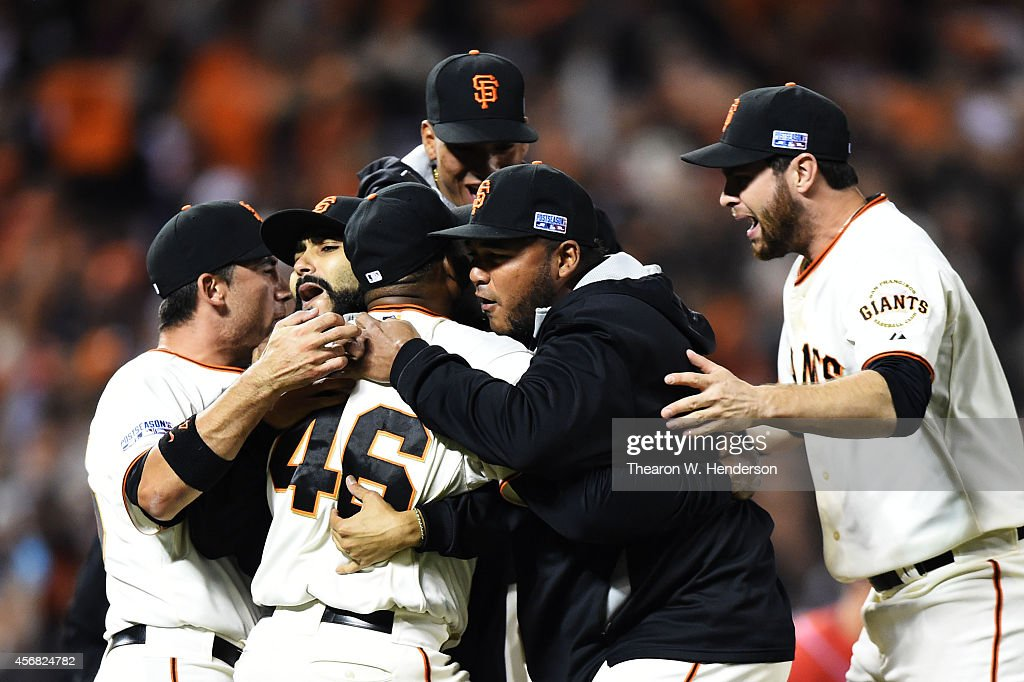 Santiago Casilla #46 of the San Francisco Giants celebrates with teammates after the final out of their 3 to 2 win over the Washington Nationals during Game Four of the National League Division Series at AT&T Park on October 7, 2014 in San Francisco, California.