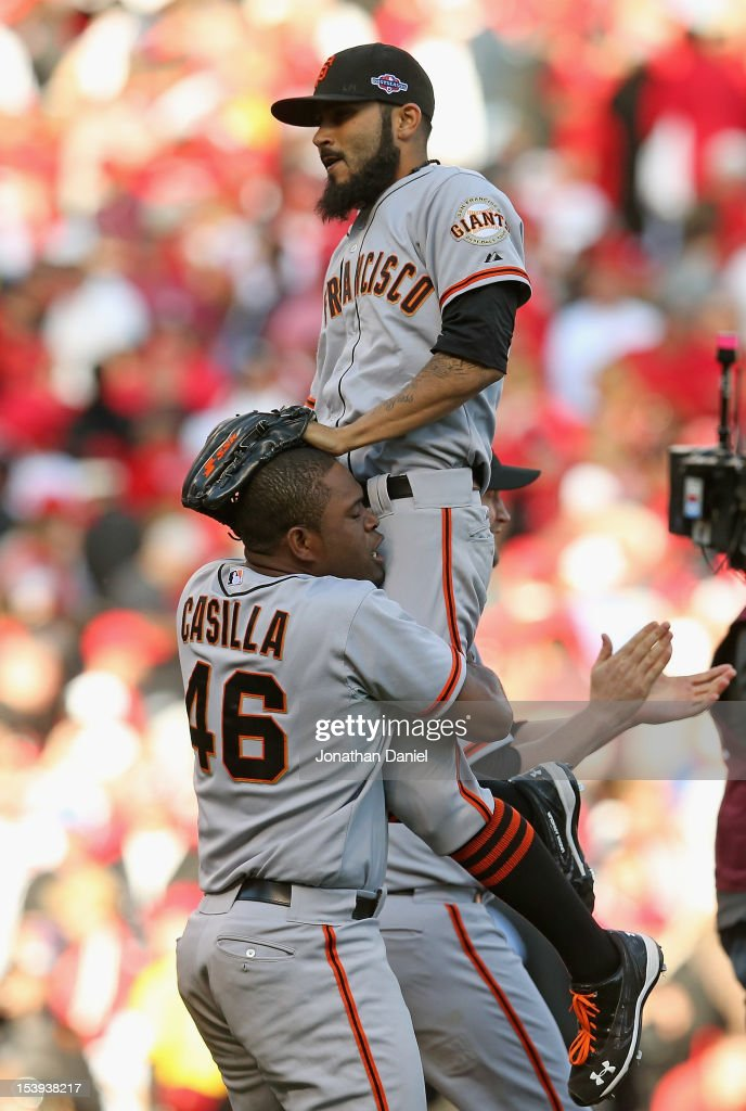 Santiago Casilla #46 of the San Francisco Giants lifts Sergio Romo #54 after a win against the Cincinnati Reds in Game Five of the National League Division Series at the Great American Ball Park on October 11, 2012 in Cincinnati, Ohio. The Giants defeated the Reds 6-4.