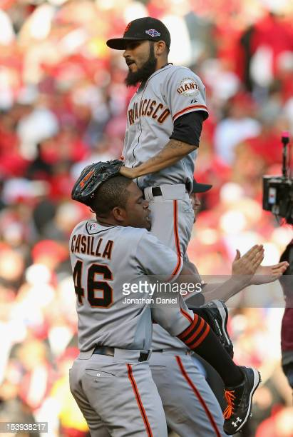 Santiago Casilla of the San Francisco Giants lifts Sergio Romo after a win against the Cincinnati Reds in Game Five of the National League Division...