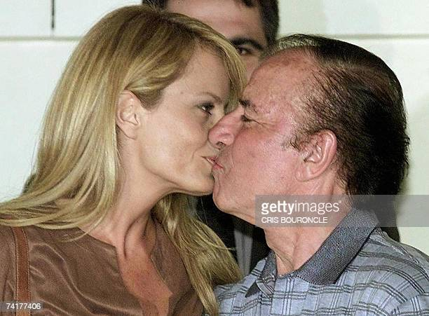 Chilean former Miss Universe and present TV host Cecilia Bolocco kisses her husband and former Argentinian President Carlos Menem 23 November 2001 in...