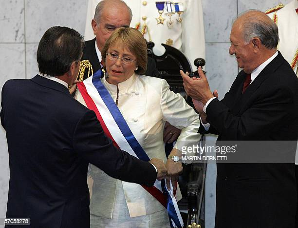 Chilean President Michell Bachelet is helped with the sash by former President Eduardo Frei while outgoing President Ricardo Lagos applauds during...