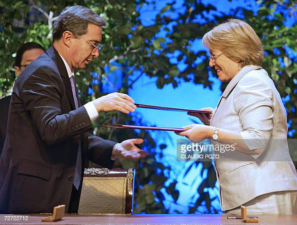Chile's President Michelle Bachelet and Colombian President Alvaro Uribe exchange documents after signing a Free Trade Agreement 27 November 2006 at...