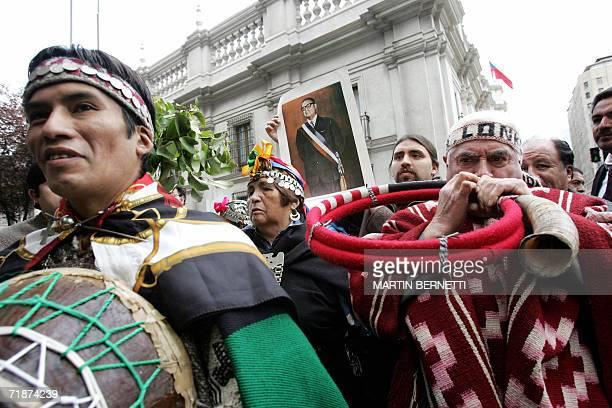 Indigenas Mapuches uno de ellos con un retrato del ex presidente Salvador Allende realizan una limpia al palacio La Moneda en Santiago el 13 de...