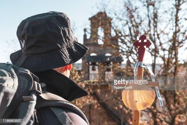 santiago de compostela way pilgrim with a hiking pole and shell looking at a church on the way. - peregrino fotografías e imágenes de stock