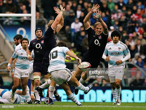 Santiago Fernandez of Argentina attempts a drop goal charged by Tom Croft and Lewis Moody of England during the Investec Challenge match between...