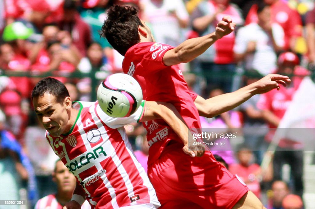 Santiago Garcia (R) of Toluca jumps for the ball with Pablo Velazquez of Necaxa during their Mexican Apertura football tournament match at the Nemesio Diez stadium in Toluca, Mexico, on August 20, 2017. /