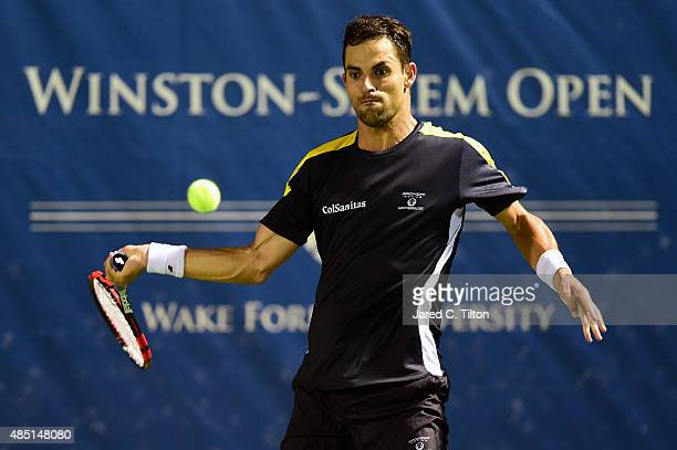 Santiago Giraldo of Colombia returns a shot from Borna Coric of Croatia during the first day of the WinstonSalem Open at Wake Forest University on...