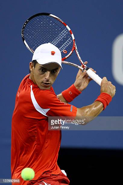 Santiago Giraldo of Colombia returns the ball against Roger Federer of Switzerland during Day One of the 2011 US Open at the USTA Billie Jean King...