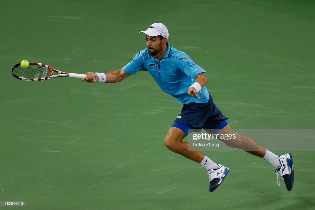Santiago Giraldo of Columbia returns a shot to John Isner of the United States during day one of the Shanghai Rolex Masters at the Qi Zhong Tennis Center on October 7, 2013 in Shanghai, China.