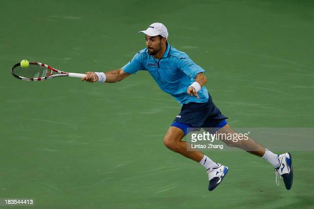 Santiago Giraldo of Columbia returns a shot to John Isner of the United States during day one of the Shanghai Rolex Masters at the Qi Zhong Tennis...