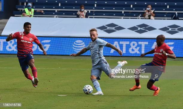 Santiago Mosquera and Fafa Picault of FC Dallas look on as Johnny Russell of Sporting Kansas City shoots on goal during a game between FC Dallas and...