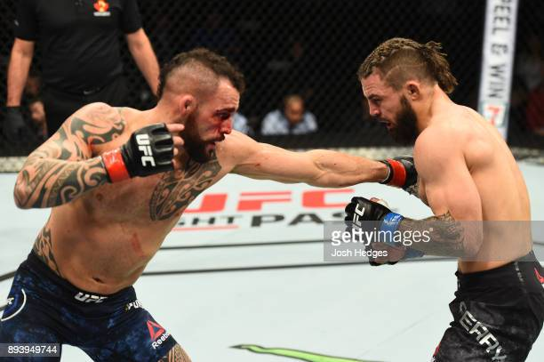 Santiago Ponzinibbio of Argentina punches Mike Perry in their welterweight bout during the UFC Fight Night event at Bell MTS Place on December 16...
