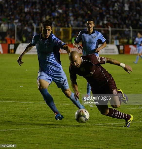 Santiago Silva of Lanús struggles for the ball with Nelson Cabrera of Bolívar during a second leg quarter final match between Bol'ívar and Lanœús as...