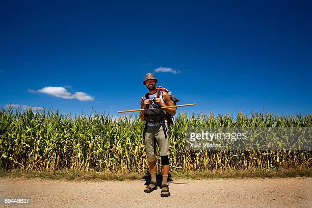 Santiago's Way Jacobean Routes French way A pilgrim wearing the typical clothes in front of some corn fields at the exit of Portomarin Lugo