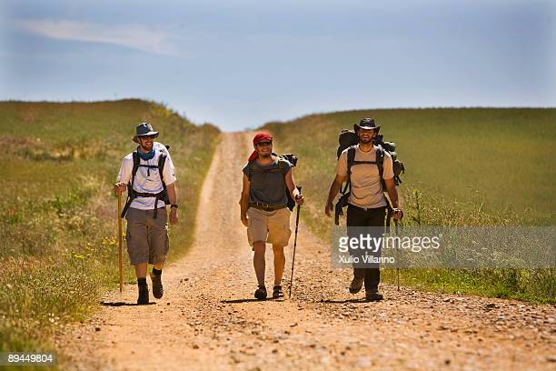 Santiago's Way Jacobean Routes French Way Pilgrims with hats on their heads to protect themselves from the sun at the entrance of Calzadilla de la...