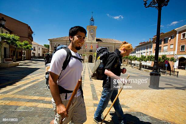 Santiago's Way Jacobean Routes French Way Two pilgrims with their rucksacks and walking sticks at the Town Hall square in Carrion de los Condes...