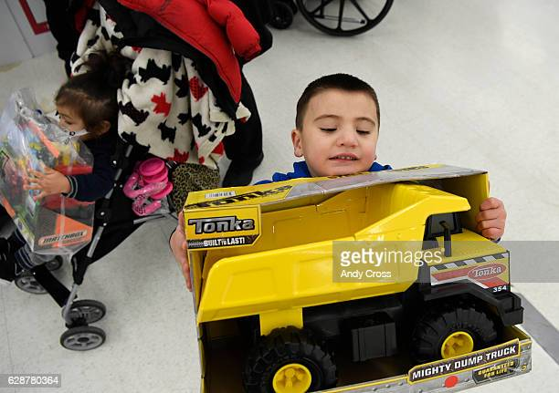 Santino Martinez holds on to his newly acquired Tonka toy truck at the 86th annual Denver Santa Claus Shop at the old Kmart store near Evans Ave and...