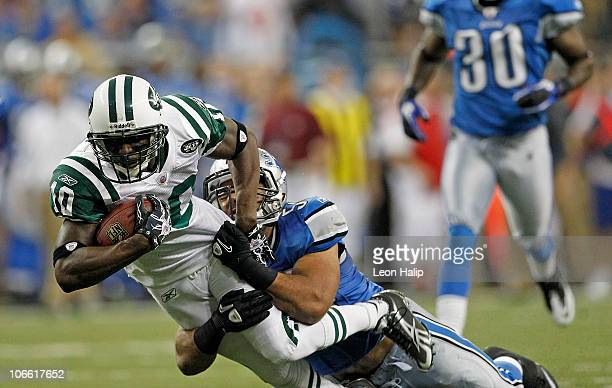 Santonio Holmes of the New York Jets catches a 54 yard pass in overtime and is tackled by Landon Johnson of the Detroit Lions during the overtime...