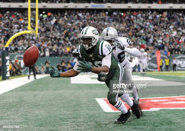 Santonio Holmes of the New York Jets misses a catch in the endzone while being defended by Phillip Adams of the Oakland Raiders during the first half...