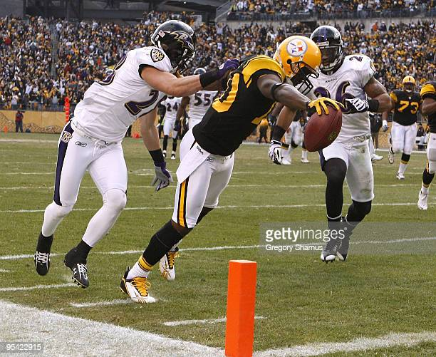 Santonio Holmes of the Pittsburgh Steelers gets in for a second quarter touchdown between Tom Zbikowski and Dawan Landry of the Baltimore Ravens on...