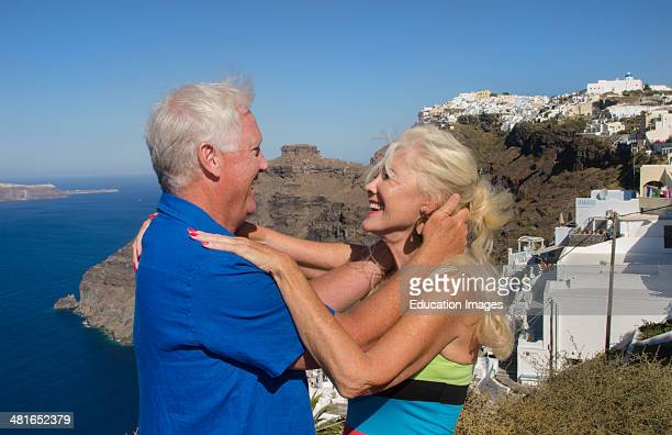 Santorini Greece retired couple on holiday having fun on cliff in Fira Greek vacation