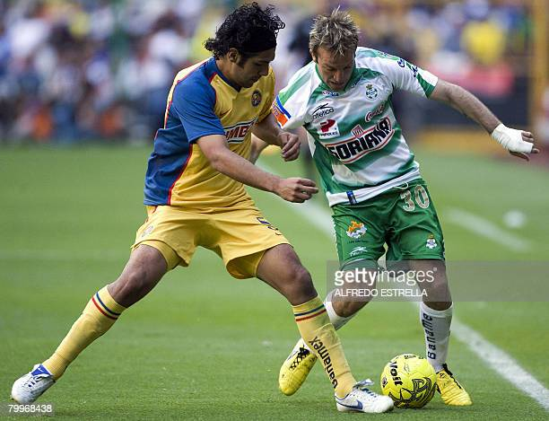 Santoss player Matias Vuoso vies for the ball with Americas player Diego Cervantes during their Mexican leagues soccer match in Mexico City on...