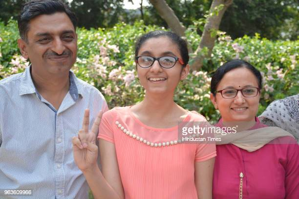 Sanya Gandhi from Uttam School for Girls with her parents pose for a picture after emerging as joint countrytopper in speciallyable category in...