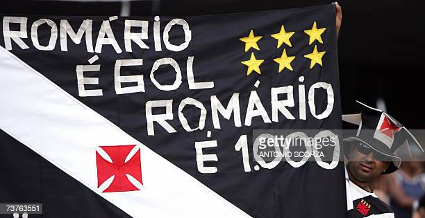 A supporter of Brazilian footballer Romario de Souza Faria holds a banner that pays tribute to the number 1000 goal of his carreer 01 April 2007 as...