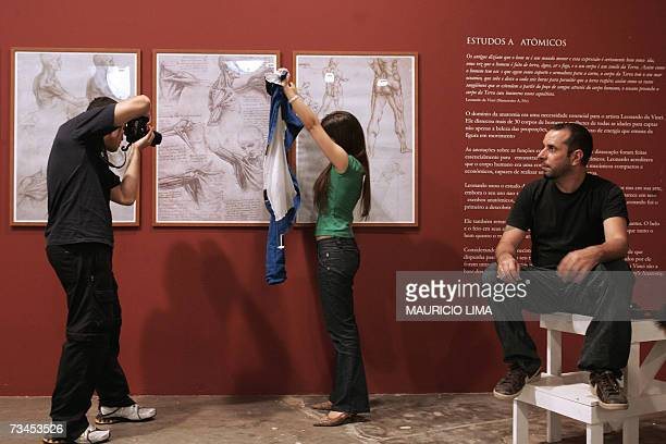 A young woman holds a photographer's jacket to block unwanted reflections on the glass of a Leonardo's framed study on anatomy he is photographing...