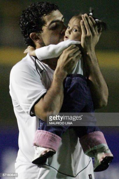 Argentine's forward Carlos Tevez of Brazil's Corinthians kisses his daugther Florencia prior to the start of a football match against Mexico's Tigres...