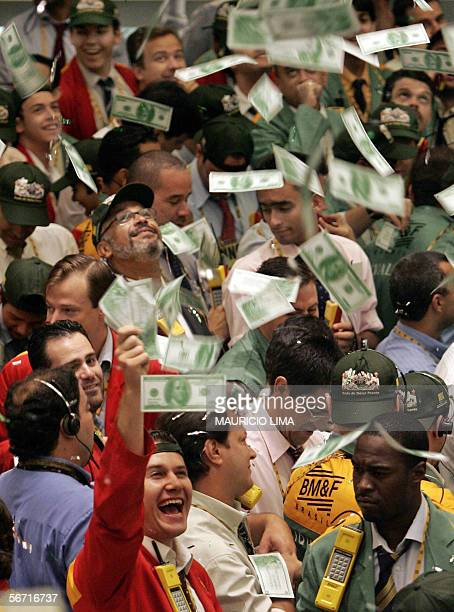 Fake US dollar notes fall from the roof over stock traders as they celebrate the launching of a new negotiation pit 'the spot dollar' moments before...