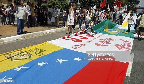 Manifestantes despliegan una bandera de Venezuela, en apoyo al presidente Hugo Chavez, pegada a un cartel con inscripciones contra la visita A bRASIL...