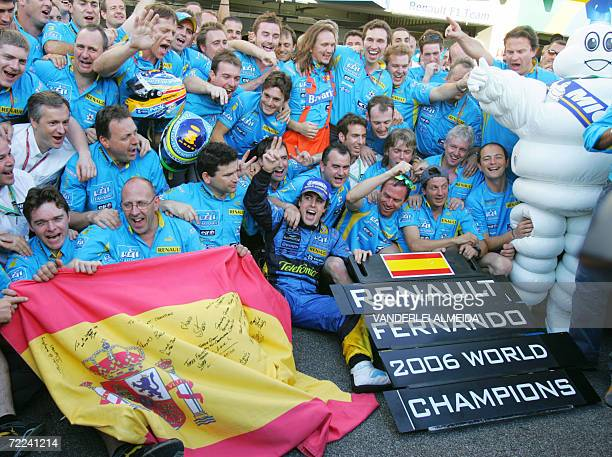 Spanish Renault driver Fernando Alonso celebrates with members of the Renault team at the Interlagos racetrack in Sao Paulo 22 October 2006 after the...