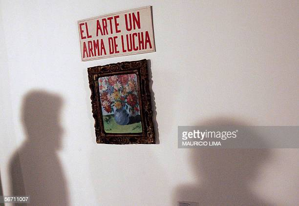 """Visitors look at Lazaro Saavedra?s painting """"El Arte un Arma de Lucha"""" during the opening session for public of """"Art of Cuba"""" exhibition, in downtown..."""