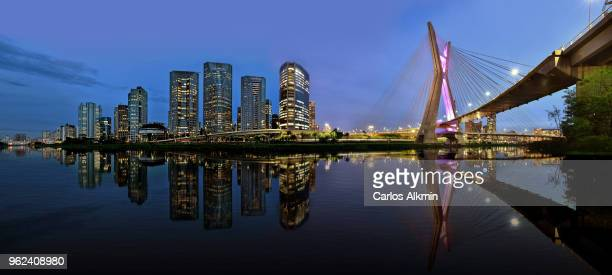 sao paulo skyline reflected on pinheiros river at blue hour - brazil stock pictures, royalty-free photos & images