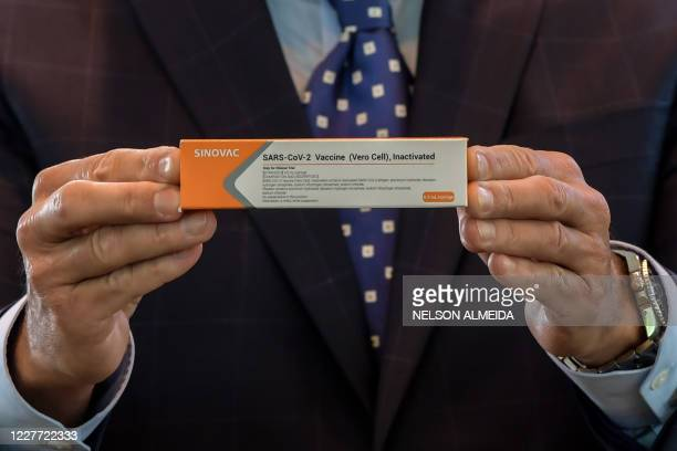 Sao Paulo State Governor Joao Doria displays a box of the COVID-19 vaccine produced by the Chinese company Sinovac Biotech at the Hospital das...