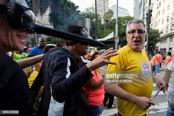 Sao Paulo's Health Secretary Alexandre Padilha jokes with two revellers dressed as mosquitos during a street carnival in the Brazilian city of Sao...