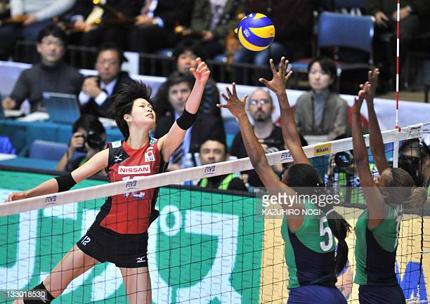Saori Kimura of Japan pushes the ball over Diana Khisa and Jannet Wanja of Kenya during a match of the World Cup women's volleyball tournament in...