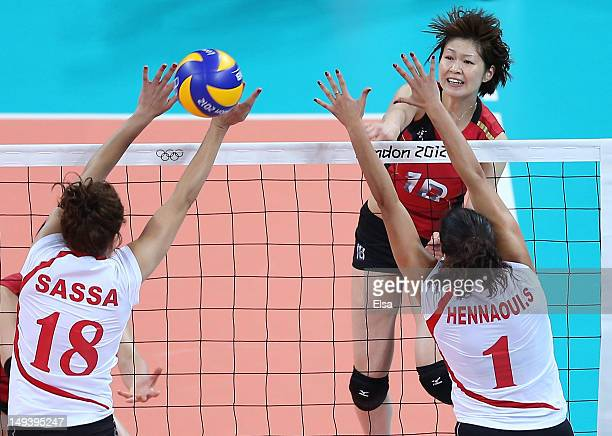Saori Kimura of Japan returns the ball as Tassadit Aissou and Sehryne Hennaoui of Algeria defend on Day 1 of the London 2012 Olympic Games at Earls...