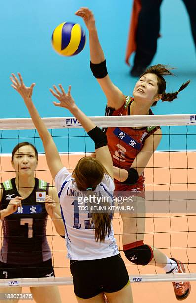 Saori Kimura of Japan spikes the ball above Thailand's Nootsara Tomkom while Japan's libero Arisa Sato looks on during their FIVB volleyball women's...