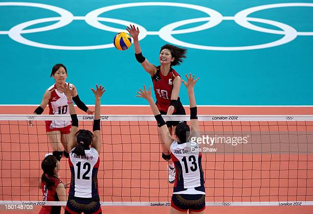 Saori Kimura of Japan spikes the ball against SongYi Han and DaeYoung Jung of Korea during the Women's Volleyball on Day 15 of the London 2012...