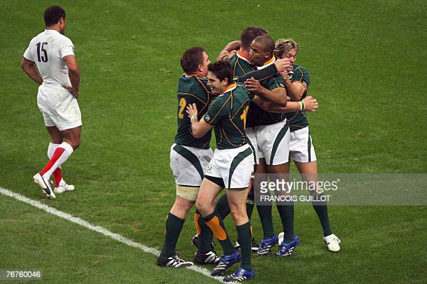 Saouth African rugby union players jubilate after a try by South Africa's winger JP Pietersen as England's fullback Jason Robinson walks away during...