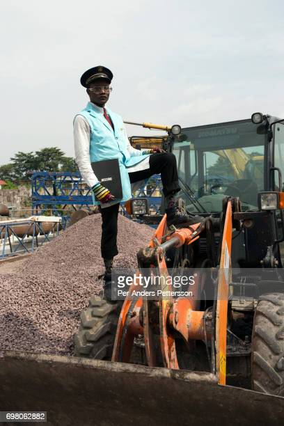 Sapeur stands at a construction site with his designer label clothes while paying his respects to Stervos Nyarcos the founder of the kitendi religion...
