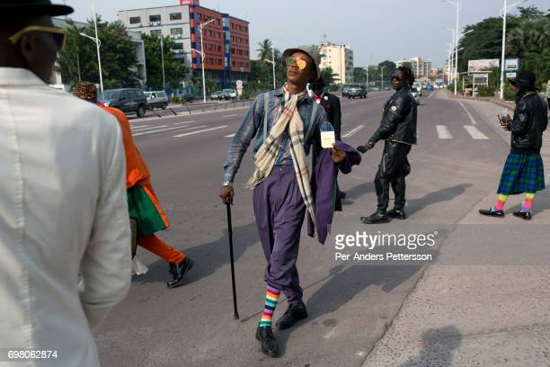 Sapeurs walk on the street with their designer label clothes while paying his respects to Stervos Nyarcos the founder of the kitendi religion which...