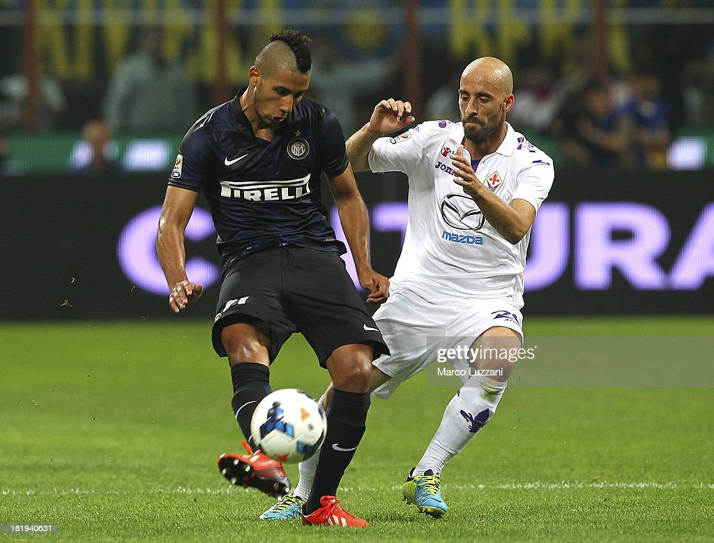 Saphir Sliti Taider of FC Internazionale Milano competes for the ball with Borja Valero of ACF Fiorentina during the Serie A match between FC Internazionale Milano and ACF Fiorentina at Giuseppe Meazza Stadium on September 26, 2013 in Milan, Italy.