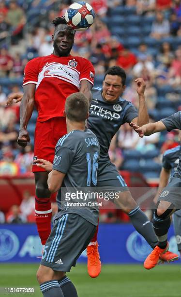 J Sapong of Chicago Fire heads the ball over Tony Rocha and James Sands of New York City FC at SeatGeek Stadium on May 25 2019 in Bridgeview Illinois...
