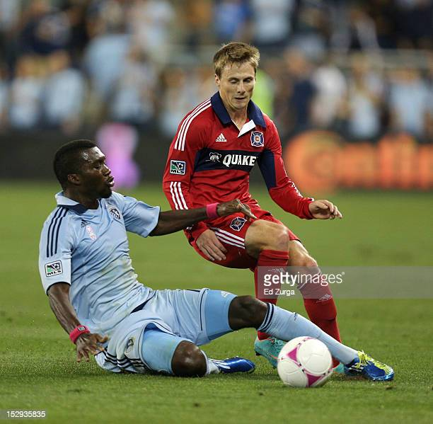J Sapong of Sporting Kansas City slides and knocks the ball away from Chris Rolfe of the Chicago Fire in the first half at Livestrong Sporting Park...