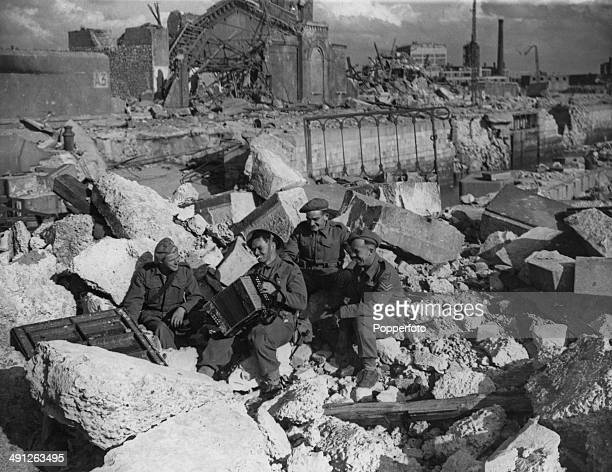 Sapper J Nicholl of the Royal Engineers plays the accordion to entertain his comrades during a lunch break at the entrance to the harbour in Calais...