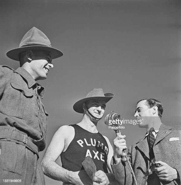 Sapper Ken Maclennan of the Australian Army is interviewed by BBC radio reporter Robert Dougall as he takes part in a wood chopping and sawing...